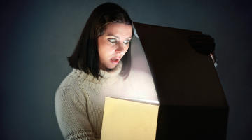 woman opening box looking scared