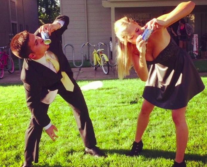 Guy and girl shotgunning beer formal