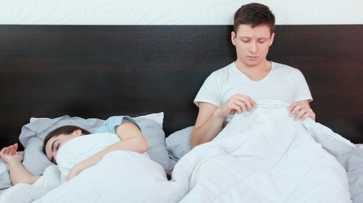 man looking at penis in bed