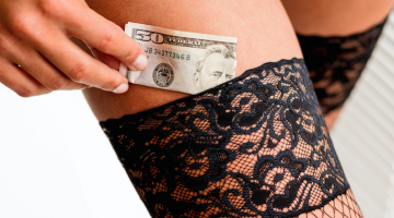 woman putting money in tights