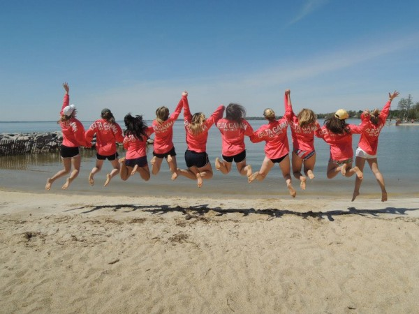 Sisters and spirit jerseys in a mid-air beach photo. TSM.