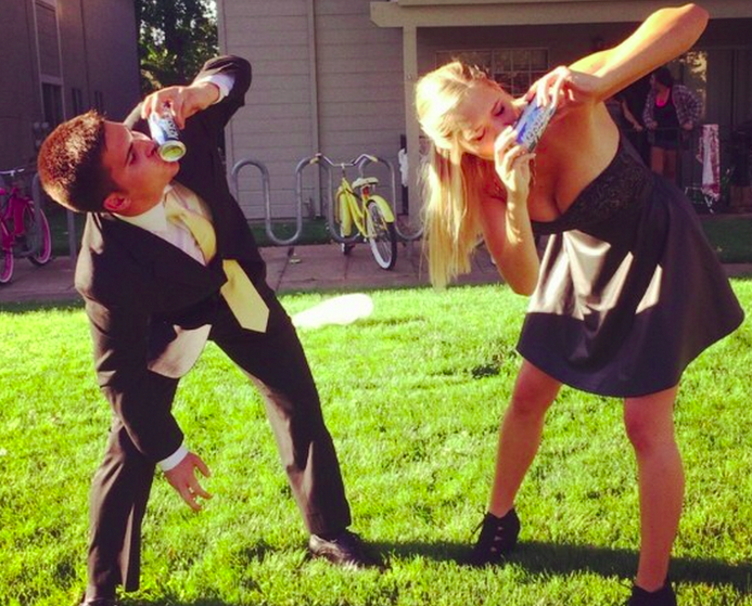 Guy and girl shotgunning beer formal