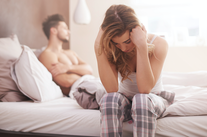 woman sitting on bed upset