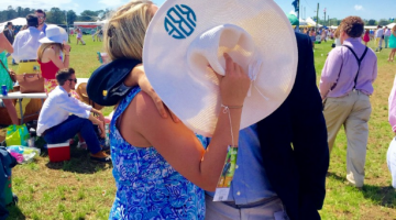 girl and guy kissing behind derby hat