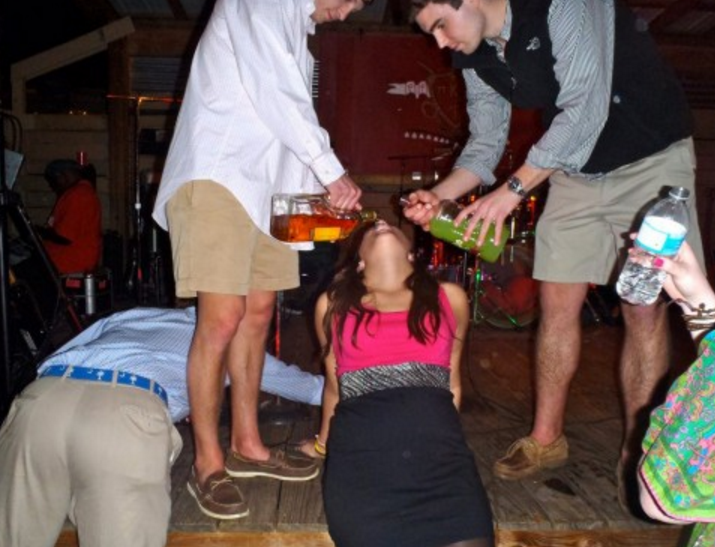 girl getting drinks poured into her mouth by college guys